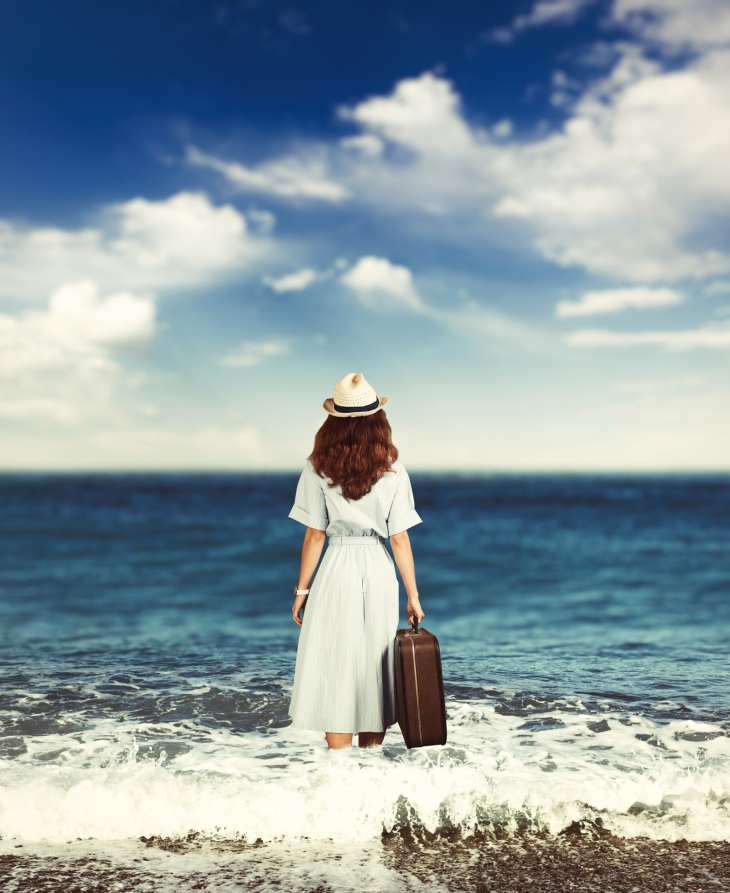 Young woman walks along the shore of the ocean.